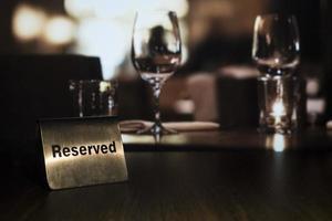 een metalen plaatje met de woorden gereserveerd staat links op een houten tafel in een restaurant met op de achtergrond een kaars en glazen foto