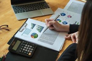 vrouwelijke zakenlieden analyseren en controleren documenten met het gebruik van computerlaptop en rekenmachine voor het berekenen van begrotingsdocumenten aan bedrijfsdirecteuren foto