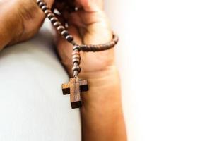 mens bidt tot god met houten rozenkrans foto