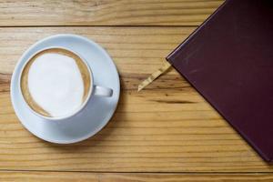 notitieboekje met kopje koffie op houten bureau foto