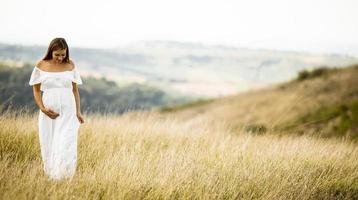 jonge zwangere vrouw op het veld foto