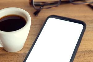 slimme telefoon op bureau met wit scherm brillen en kopje koffie op houten tafel mock-up sjabloon foto