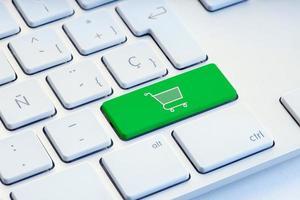 online winkelen e-commerce internet shopping concept winkelwagentje pictogram op groene toets op het toetsenbord foto