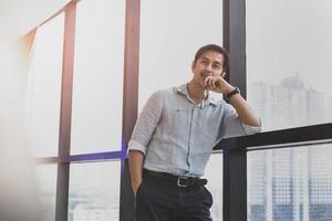 knappe Aziatische man die in modern gebouw naast groot raam foto