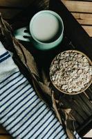 kopje havermelk met haverzaad op een kom boven een houten plank foto