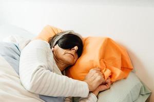 een oude dame slaapt met een gezichtsmasker in een moderne slaapkamer met kopie ruimte foto