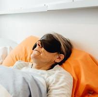een oude dame slaapt met een gezichtsmasker in een moderne slaapkamer foto
