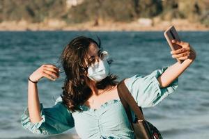 jonge vrouw op het strand met behulp van een masker tijdens het nemen van een selfie lifestyle concept zomerstijl foto