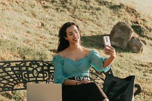 jonge vrouw die een selfie op een bankje van de zomerstijl van het parklevensstijl neemt foto