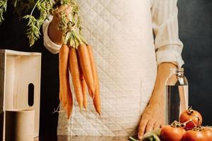 vrouw met wortelen en groenten foto