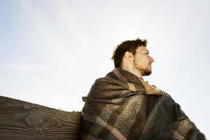 zijgezicht van een jonge man met de ogen dicht die rustig geniet van de ochtendherfstzon met de achtergrondverlichting van de blauwe lucht foto