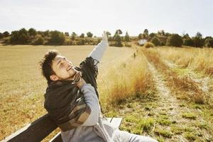 een jonge man met uitgestrekte armen en een warme sjaal die geniet van de ochtendherfstzon in een geel veld met de achtergrondverlichting van de blauwe lucht foto