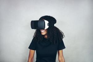 een mooie jonge zwarte vrouw met krullend afro haar draagt een virtual reality vr-headset en speelt videogames terwijl ze lacht in de studio met een grijze achtergrond foto