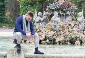 jonge man zit in de fontein van een park en kijkt naar zijn mobiele telefoon foto