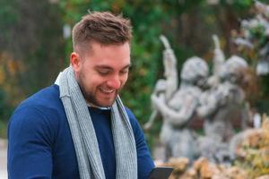 jonge man glimlachend in een park zijn mobiele telefoon controleren foto