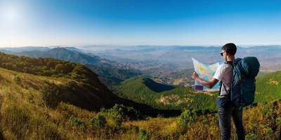 reiziger met kaart rugzak ontspannen buiten met bergen foto