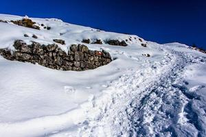 pad tussen sneeuw en rotsen foto