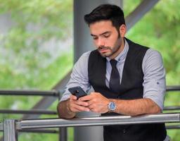 knappe zakenman permanent op een smartphone foto