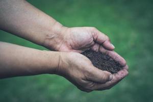 Aziatische vrouw met turfmos organische stof verbetert de bodem voor het kweken van tuinbouwgewassen foto