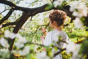 jonge bruid met blond haar die zich voordeed op de achtergrond van de lente boomgaard foto