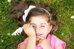 klein meisje tot in het gras foto