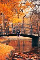 twee kleine meisjes zittend op een houten brug en doen alsof vissen herfst achtergrond foto