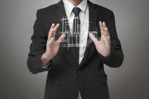 zakenman met een model van het huis foto