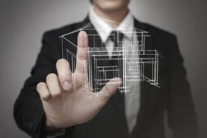 zakenman virtueel scherm een model van het huis aan te raken foto