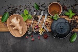 zwarte gietijzeren theepot met kruidenthee ingesteld op donkere stenen achtergrond foto
