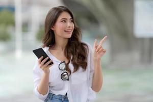 portret van een jonge vrouw met een lachebekje met behulp van een telefoon loopt in een stad foto