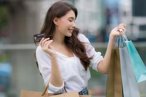 buitenshuis portret van gelukkige vrouw met boodschappentassen en lachend gezicht foto