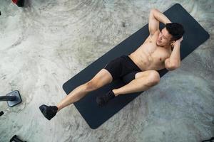 sportieve man training doen oefening in fitness gym foto