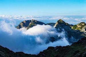 wolken tussen bergen foto