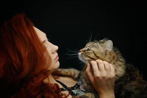 roodharige vrouw knuffelt en strijkt pluizige kat foto