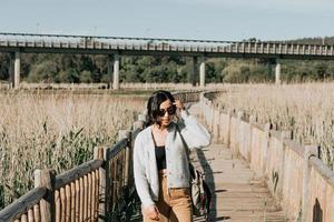 vrouw met behulp van een zonnebril glimlachen naar de camera terwijl in het land foto