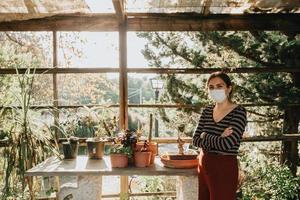 een vrouw met een masker aan het tuinieren tijdens een superzonsondergang foto