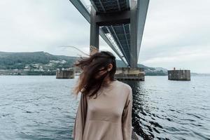 portret van een vrouw met bewegend haar onder een brug foto