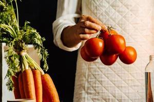 vrouw met tomaten en groenten boven een tafel met water foto