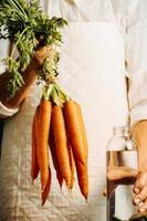 vrouw met wortelen en groenten boven een tafel met water foto