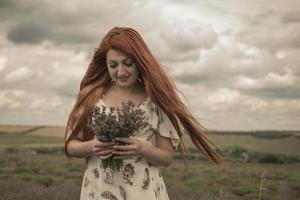 portret van een roodharig jong meisje in een witte jurk in een veld met een boeket lavendel foto
