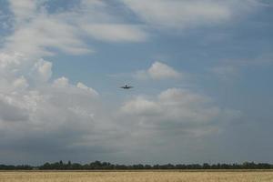 het vliegtuig komt aan boord vliegend over het veld met tarwe foto