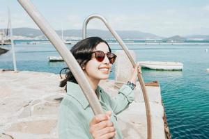 jonge vrouw op een aanlegsteiger lachend tijdens een zonnige dag foto