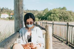jonge vrouw met behulp van een zonnebril en een gezichtsmasker tijdens het gebruik van een telefoon foto