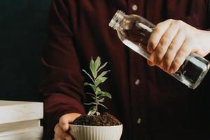 close-up van een man die op het punt staat een plant water te geven foto