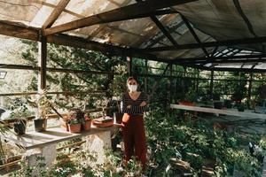 een vrouw met een masker aan het tuinieren foto