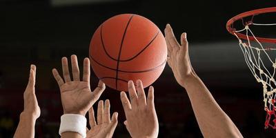 basketbalbal vliegt met basketbalring over een basketbalveld foto
