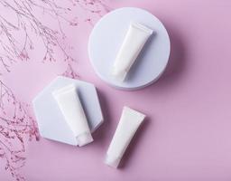 witte buisjes crème op een roze achtergrond foto
