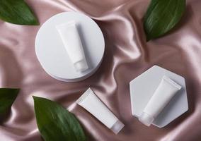 witte buisjes crème op een lichtbruine zijden achtergrond foto