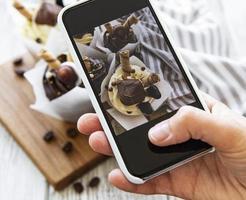 meisje maakt een foto van cupcakes op een smartphone