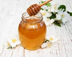 honing met jasmijnbloemen op een houten achtergrond foto